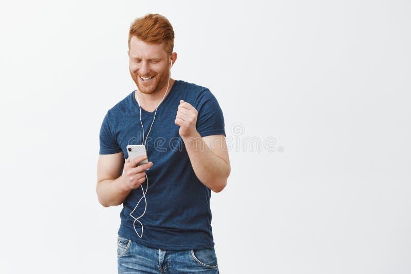 Het aanzetten vibes van de zomer Blij onbezorgd knap rijp mannetje met rode haar en spieren, die smartphone houden royalty-vrije stock afbeeldingen