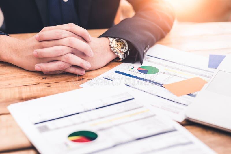 Het abstracte beeld van de zowel handen van document van de zakenman als het bedrijfsgrafiek op de houten lijst tijdens zonsopgan royalty-vrije stock fotografie