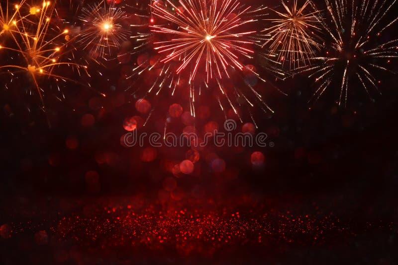 Het abstracte goud, zwart en het rood schitteren achtergrond met vuurwerk Kerstmisvooravond, vierde van juli-vakantieconcept stock foto's
