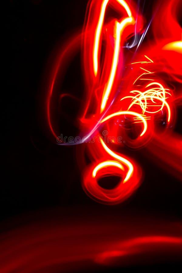 Het abstracte rode oranje motief lichte schilderen op zwarte achtergrond stock foto