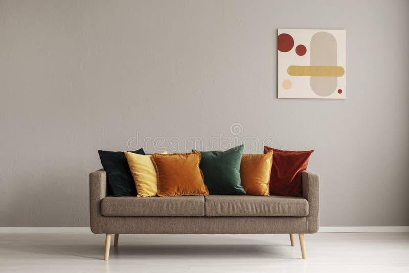 Het abstracte schilderen op grijze muur van retro woonkamerbinnenland met beige bank met hoofdkussens royalty-vrije stock fotografie