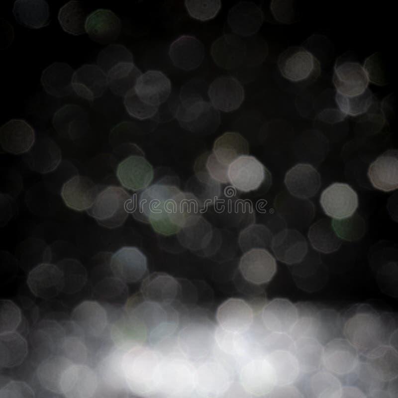 Het abstracte witte zilver schittert bokeh defocused textuurachtergrond op zwarte stock foto