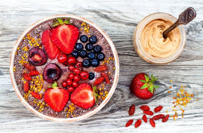 Het Acaiontbijt superfoods smoothies werpt met chiazaden, bijenstuifmeel, de bovenste laagjes van de gojibes en pindakaas lucht stock foto's