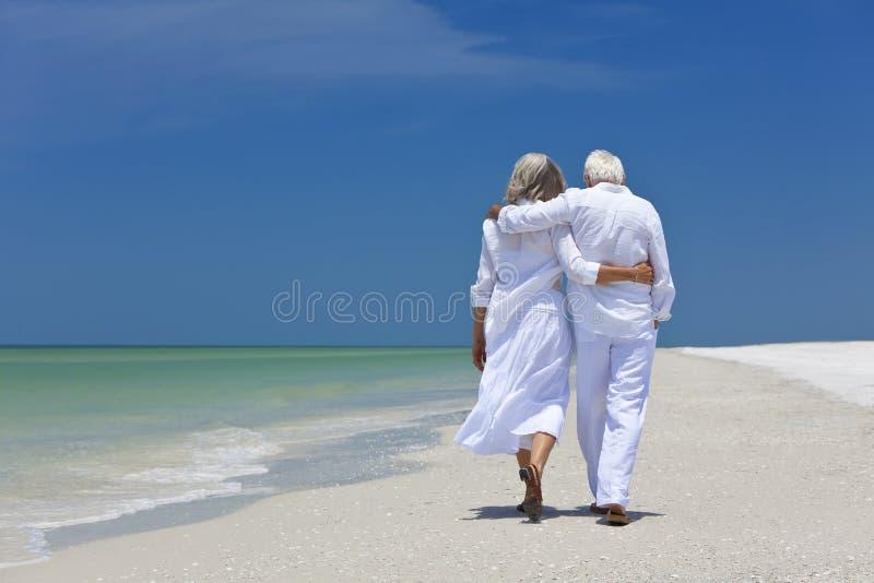 Het achter Hogere Paar dat van de Mening op Tropisch Strand loopt stock afbeeldingen