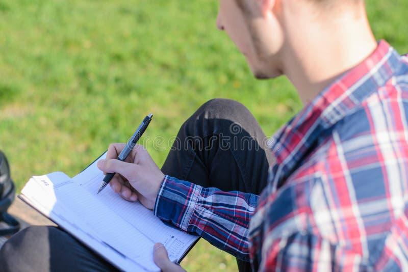 Het achterachtergedeelte achter mening bebouwde foto van ernstige geconcentreerde slimme kerel makend nota's aan zijn notitieboek stock foto's