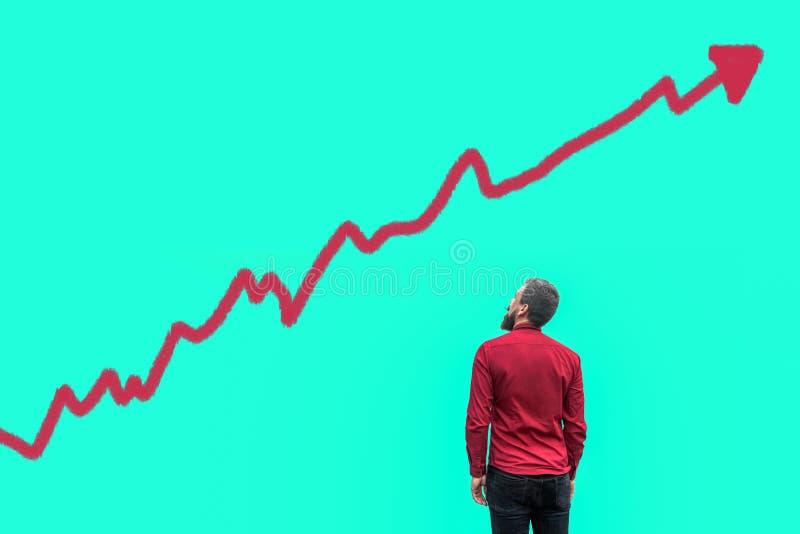 Het achtereind van jonge gebaarde knappe zakenman in rood overhemd die en zich het kweken van de analysediagram van de grafiekgra stock foto's