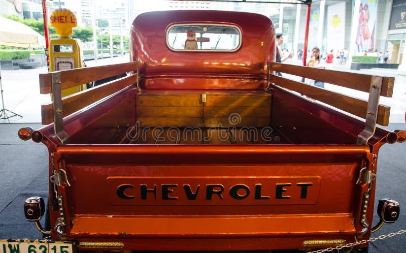 Het Achtergedeelte van Uitstekende Chevrolet-pick-up in sinaasappel heeft parkeren als decoratie bij een Zippy Markt, Centraal we royalty-vrije stock foto