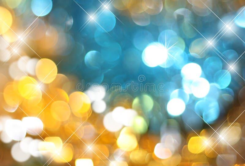Het achtergrondgoud met blauwe gloeiende lovertjes, het blauw van Zolotoy en het fonkelen schitteren, vage feestelijke achtergron stock foto's
