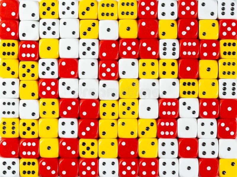 Het achtergrondpatroon van willekeurige bevolen wit, rood en geel dobbelt stock afbeelding