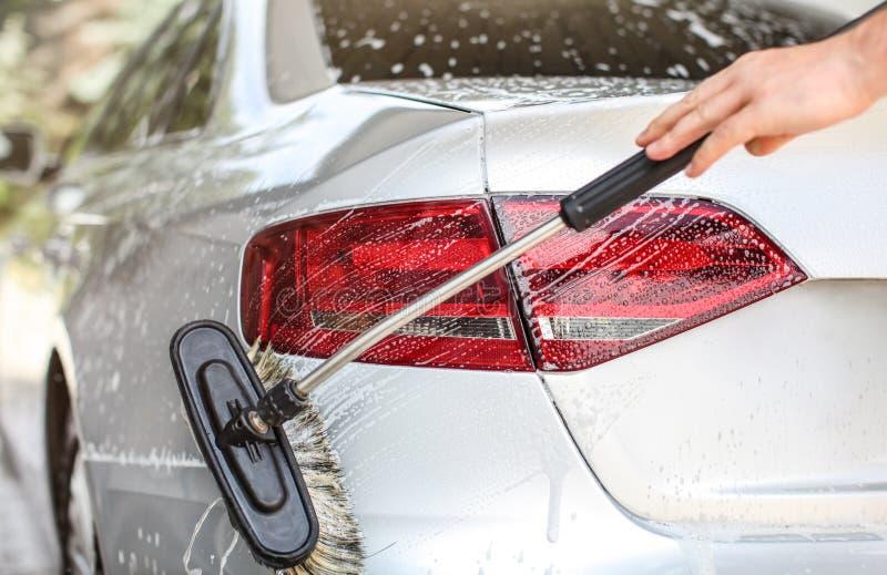 Het achterlicht en rug van zilveren die auto in zelf wordt de gewassen dienen handcarwash Borstel het schoonmaken shampoo behande royalty-vrije stock foto's