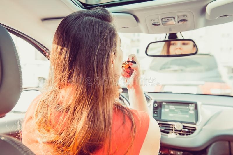 Het achtermenings jonge vrouw kijken in achteruitkijkspiegel en het zetten maken omhoog in auto het moderne bezige leven mooie me stock afbeelding