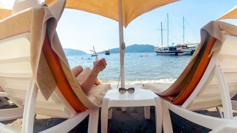 Het achtermeningsbeeld van het mooie jonge vrouw liggen sunbed met cocktail stock fotografie