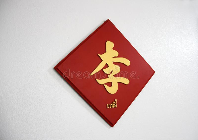 Het achternaamteken op de witte muur, de gouden Chinese stijl van het woordhandschrift op het rode houten teken royalty-vrije stock foto