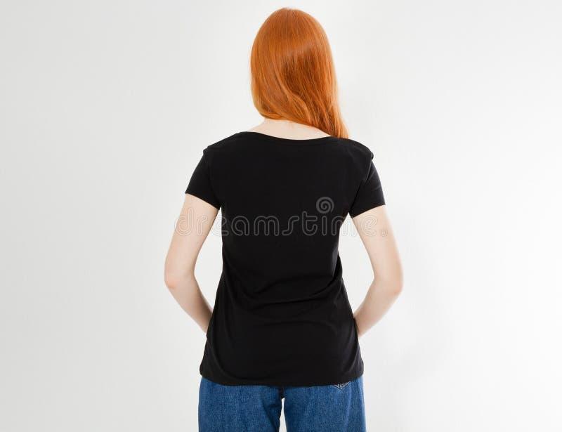Het achterontwerp van de meningst-shirt, gelukkig mensenconcept - glimlachende rode haarvrouw die in lege zwarte t-shirt haar vin stock foto