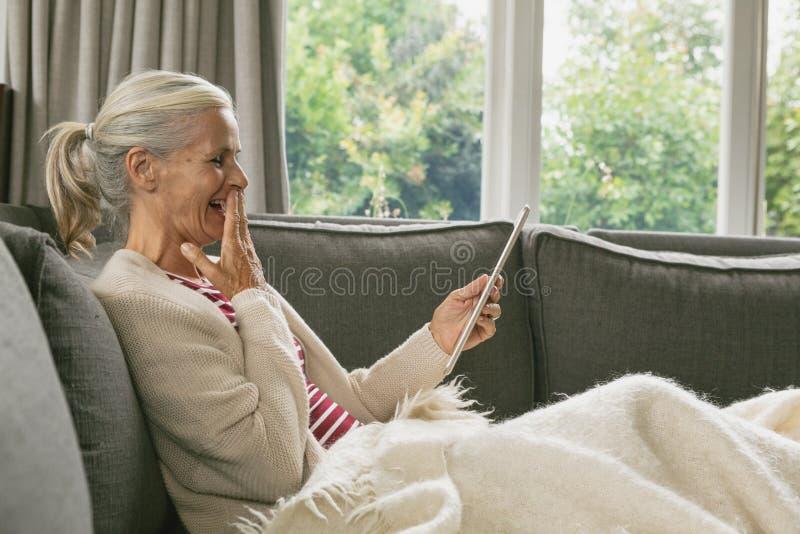 Het actieve hogere vrouw ontspannen op bank en het gebruiken van digitale tablet in woonkamer bij comfortabel huis royalty-vrije stock foto