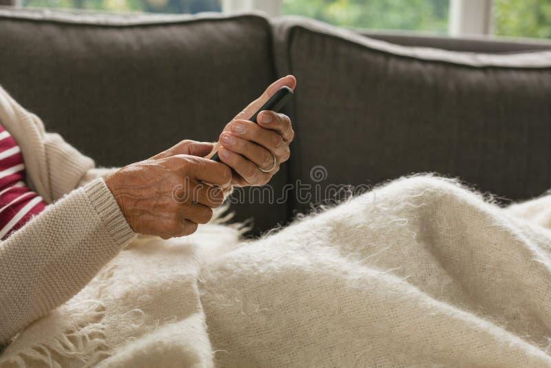 Het actieve hogere vrouw ontspannen op bank en het gebruiken van laptop in woonkamer bij comfortabel huis stock afbeelding