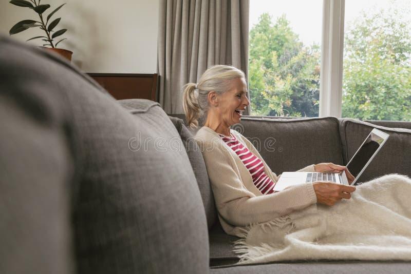 Het actieve hogere vrouw ontspannen op bank en het gebruiken van laptop in woonkamer bij comfortabel huis stock foto