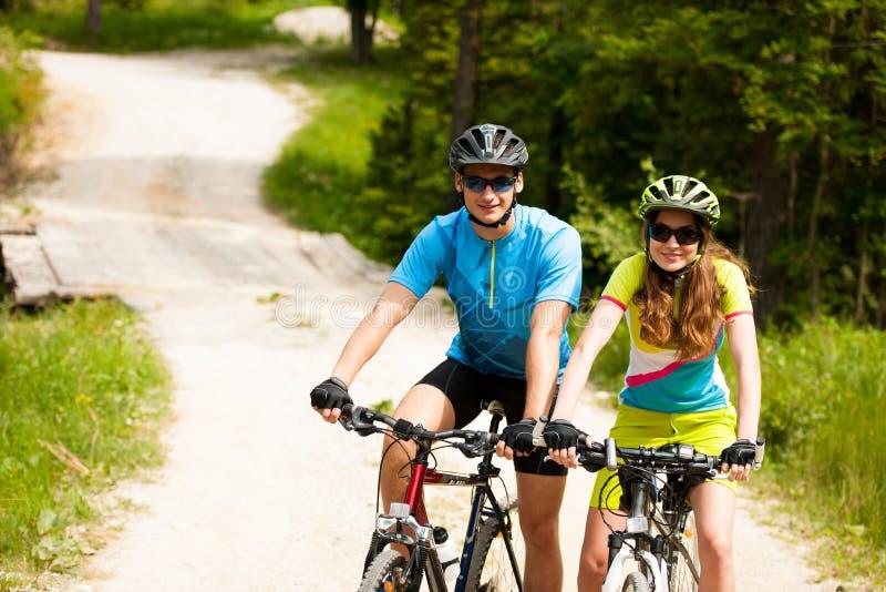 Het ACTIEVE Jonge paar biking op een bosweg in berg op een spr stock afbeelding