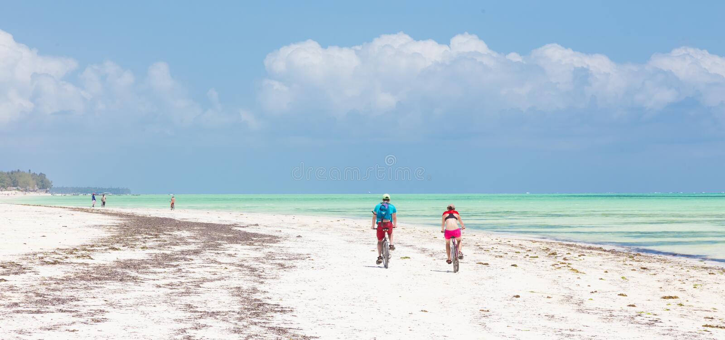 Het actieve sportieve toeristenpaar cirkelen onderaan tropische strand van het beeld het perfecte witte zand van Paje, Zanzibar,  stock afbeelding