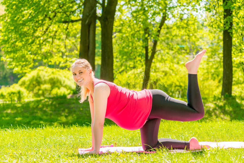 Het actieve zwangere meisje is bezig geweest met gymnastiek in het park royalty-vrije stock fotografie