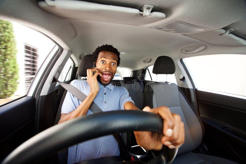 Het afgeleide mens drijven in auto die op slimme telefoon spreken stock fotografie
