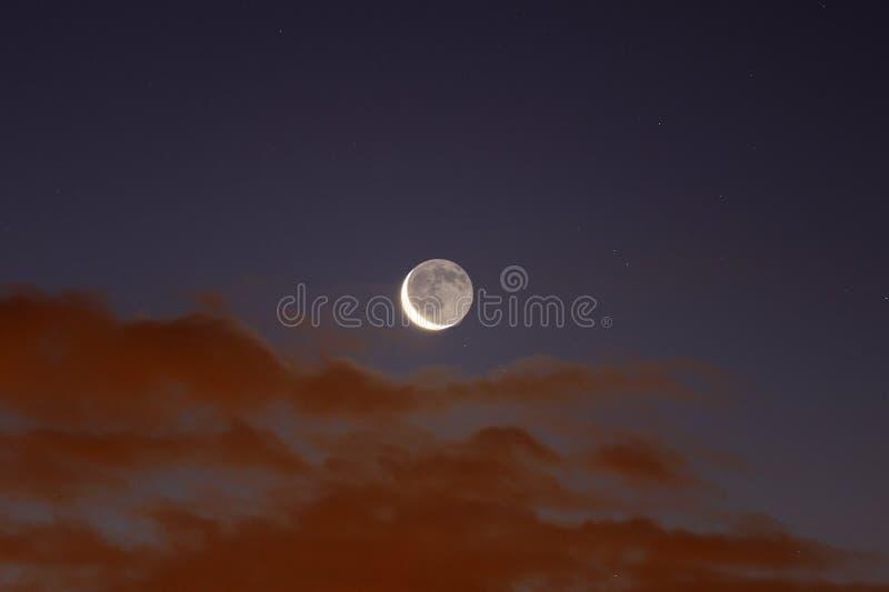 Het afnemen Crescent Moon speelt met wolken bij dageraad stock afbeeldingen
