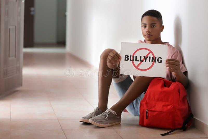 Het afrikaans-Amerikaanse blad van de tienerholding van document met woord die terwijl het zitten op vloer op school INTIMIDEREN royalty-vrije stock afbeelding