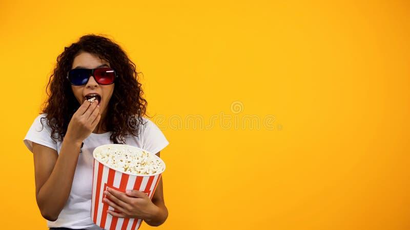 Het afrikaans-Amerikaanse meisje in 3d glazen met popcorn het letten op komedie toont, malplaatje stock foto