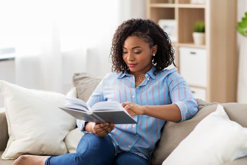Het Afrikaanse Amerikaanse boek van de vrouwenlezing thuis stock fotografie