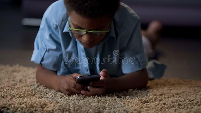 Het Afrikaanse Amerikaanse jong geitje spelen in toepassing op telefoon die comfortabel op vloer liggen royalty-vrije stock afbeelding