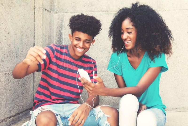 Het Afrikaanse Amerikaanse jonge volwassen paar houdt van muziek royalty-vrije stock fotografie