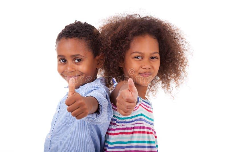 Het Afrikaanse Amerikaanse jongen en meisjes maken beduimelt omhoog gebaar - Zwart p stock afbeeldingen