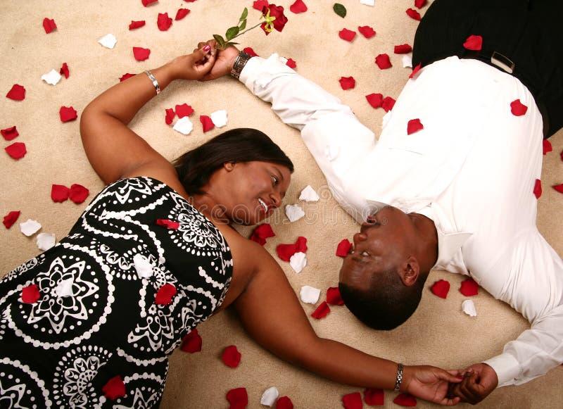 Het Afrikaanse Amerikaanse Leggen van het Paar stock fotografie