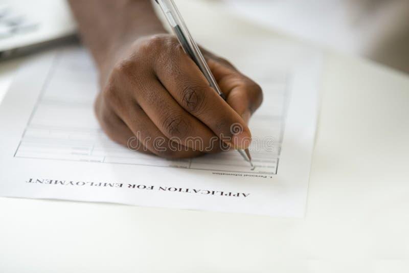 Het Afrikaanse Amerikaanse mens het vullen werkgelegenheidsaanvraagformulier, sluit stock afbeeldingen
