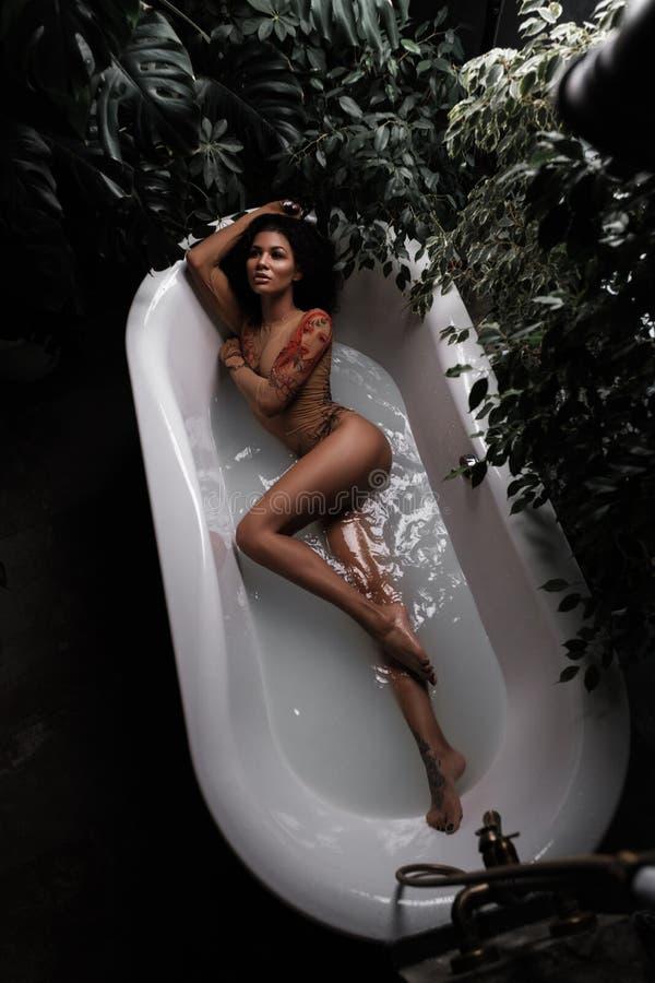Het Afrikaanse Amerikaanse mooie vrouwelijke model met slank schitterend lichaam ligt en stelt in het badhoogtepunt van water in  stock afbeeldingen