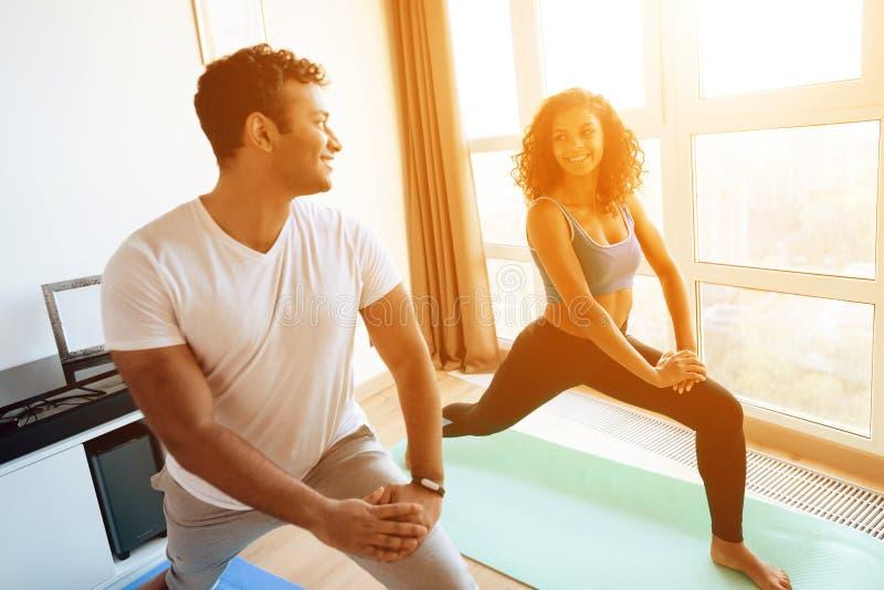 Het Afrikaanse Amerikaanse paar die yoga doen oefent thuis uit Zij bevinden zich op de vloer op yogamatten royalty-vrije stock fotografie