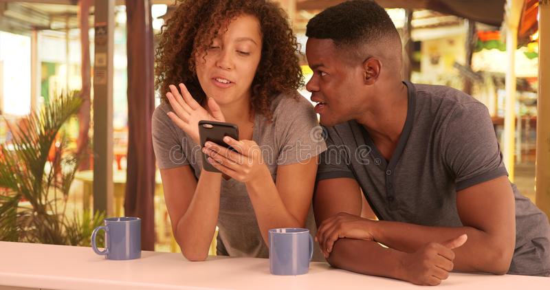 Het Afrikaanse Amerikaanse paar gebruikt hun slimme telefoon terwijl bij een koffie royalty-vrije stock foto's