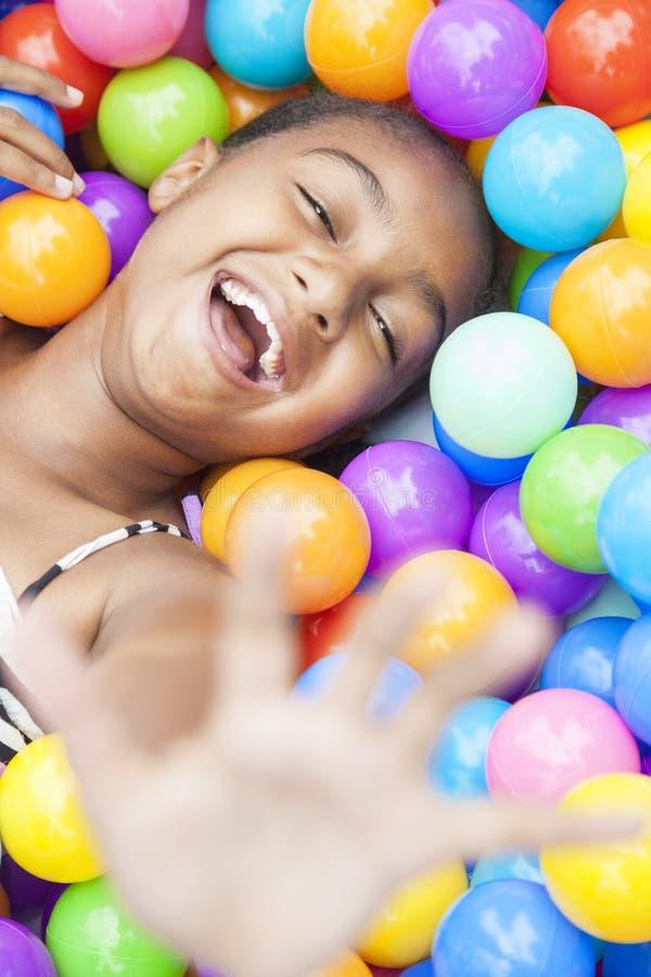 Het Afrikaanse Amerikaanse Spelen van het Meisje in Gekleurde Ballen royalty-vrije stock afbeelding