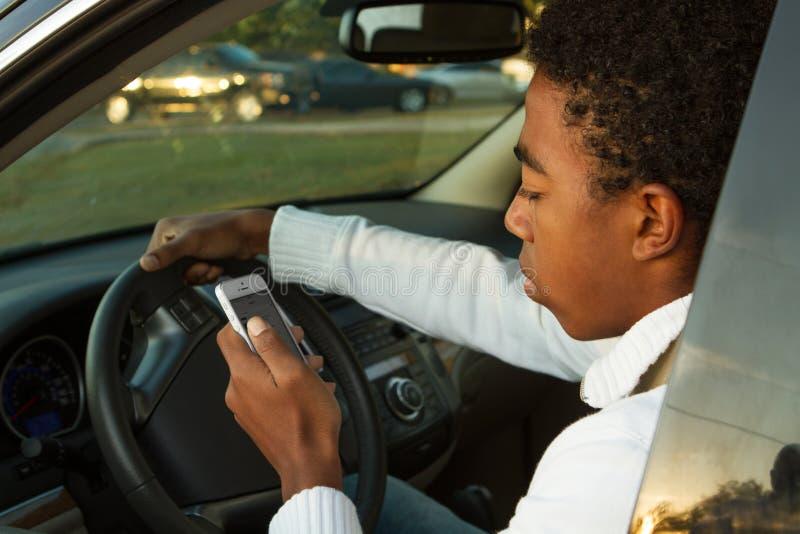 Het Afrikaanse Amerikaanse Tiener texting in een auto stock foto's