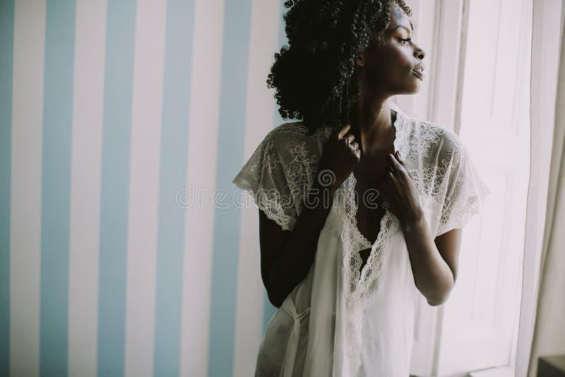 Het Afrikaanse Amerikaanse vrouw stellen in de ruimte door het venster royalty-vrije stock afbeeldingen