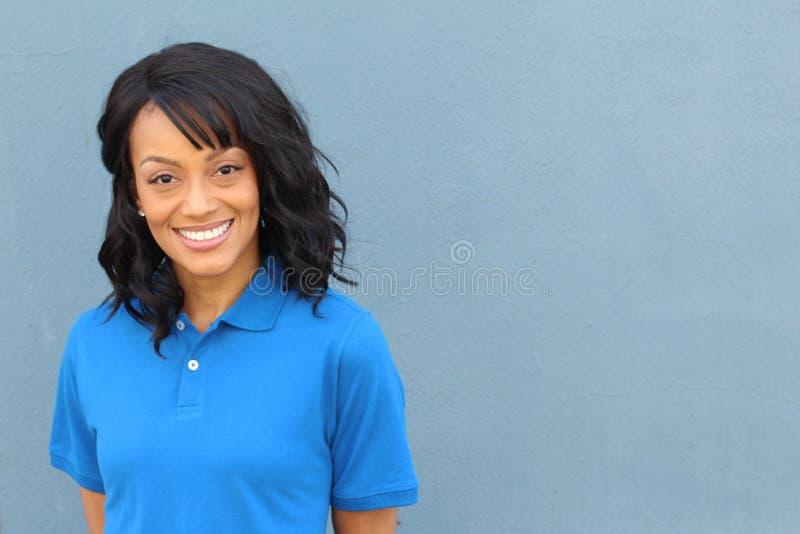 Het Afrikaanse Amerikaanse vrouwelijke handarbeider stellen in eenvormige kruising geïsoleerd op blauw stock fotografie