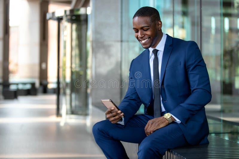 Het Afrikaanse Amerikaanse zakenman vrolijk glimlachen, gebruikend celtelefoon bij de bureaubouw, Internet, breedband, 5G, exempl stock afbeelding