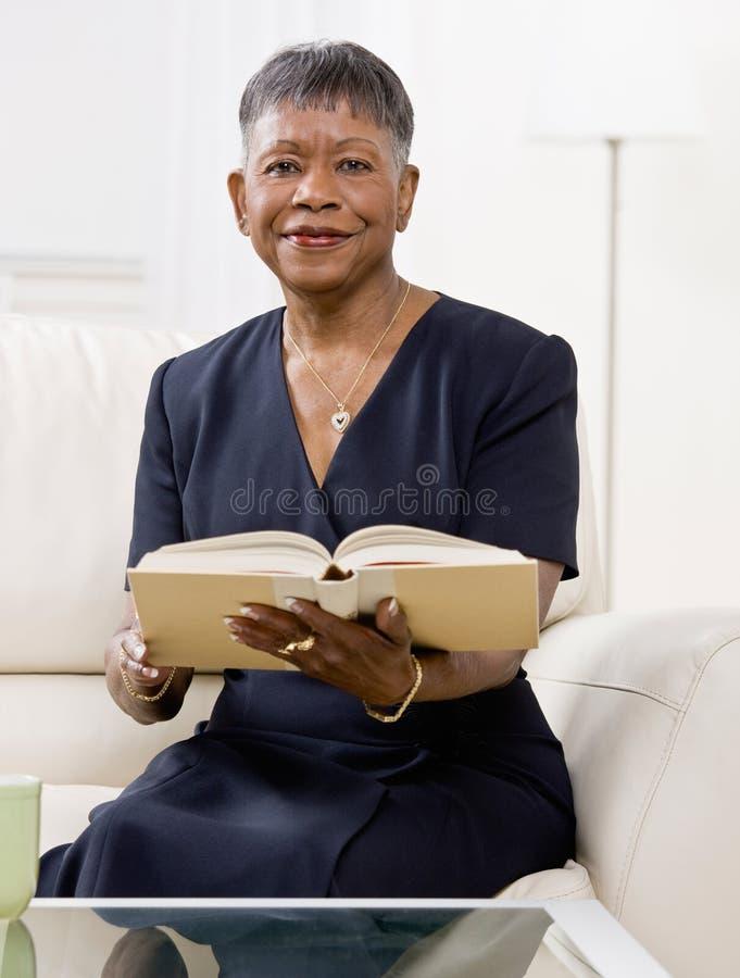 Het Afrikaanse boek van de vrouwenlezing op bank in woonkamer stock foto's