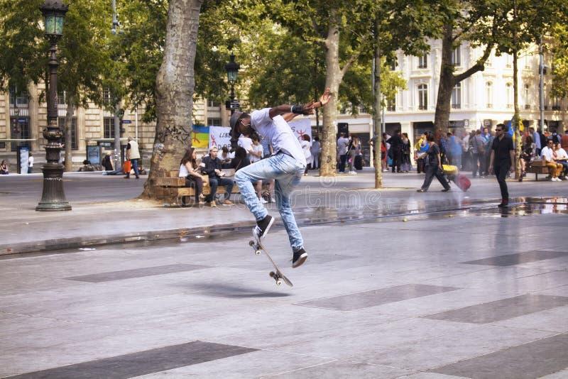 Het Afrikaanse Franse jonge mannetje springt terwijl het schaatsen royalty-vrije stock afbeeldingen