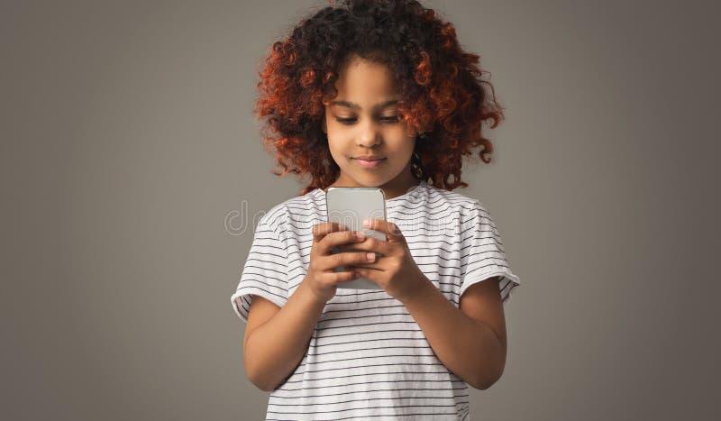 Het Afrikaanse jong geitjemeisje spelen op smartphone op grijze achtergrond royalty-vrije stock afbeeldingen