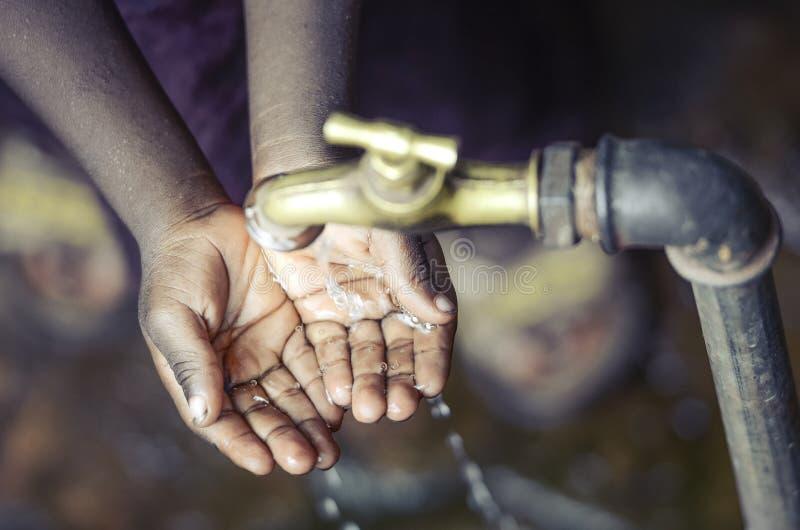 Het Afrikaanse Kind met Handen vormde onder Waterkraan tot een kom in Bamako stock fotografie
