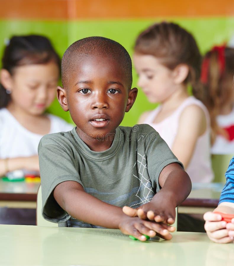 Het Afrikaanse kind spelen met deeg stock afbeeldingen