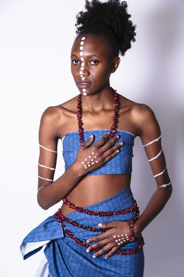 Het Afrikaanse meisje met gezichtskunst zette haar hand op hart stock foto
