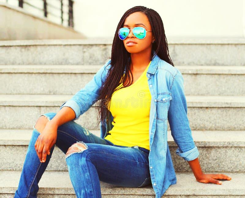Het Afrikaanse vrouw dragen zonnebril en jeansoverhemd stock afbeeldingen