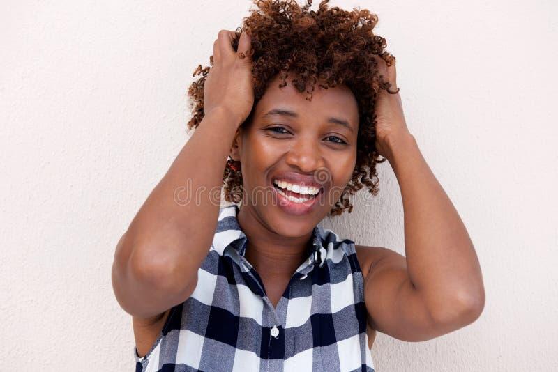 Het Afrikaanse vrouw glimlachen met dient haar in royalty-vrije stock foto